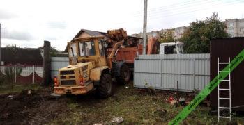 Трактор грузит пни на самосвал для вывоза